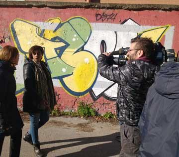 Foto di Hermon Tesfamicael con la giornalista e il cameraman durante l'intervista a Officina Giovani
