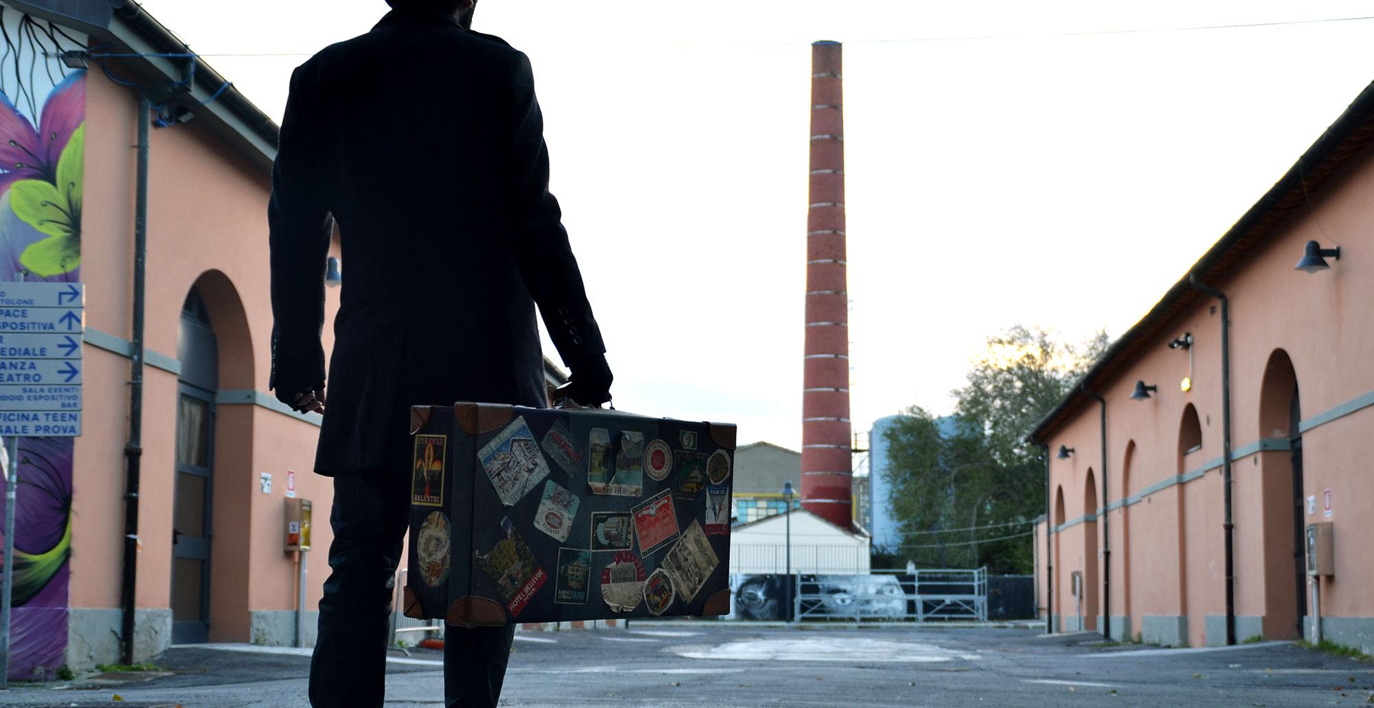 Foto a colori negli spazi esterni centrali di Officina Giovani con uomo con cappotto scuro e valigia in mano e sullo sfondo una ciminiera rossa