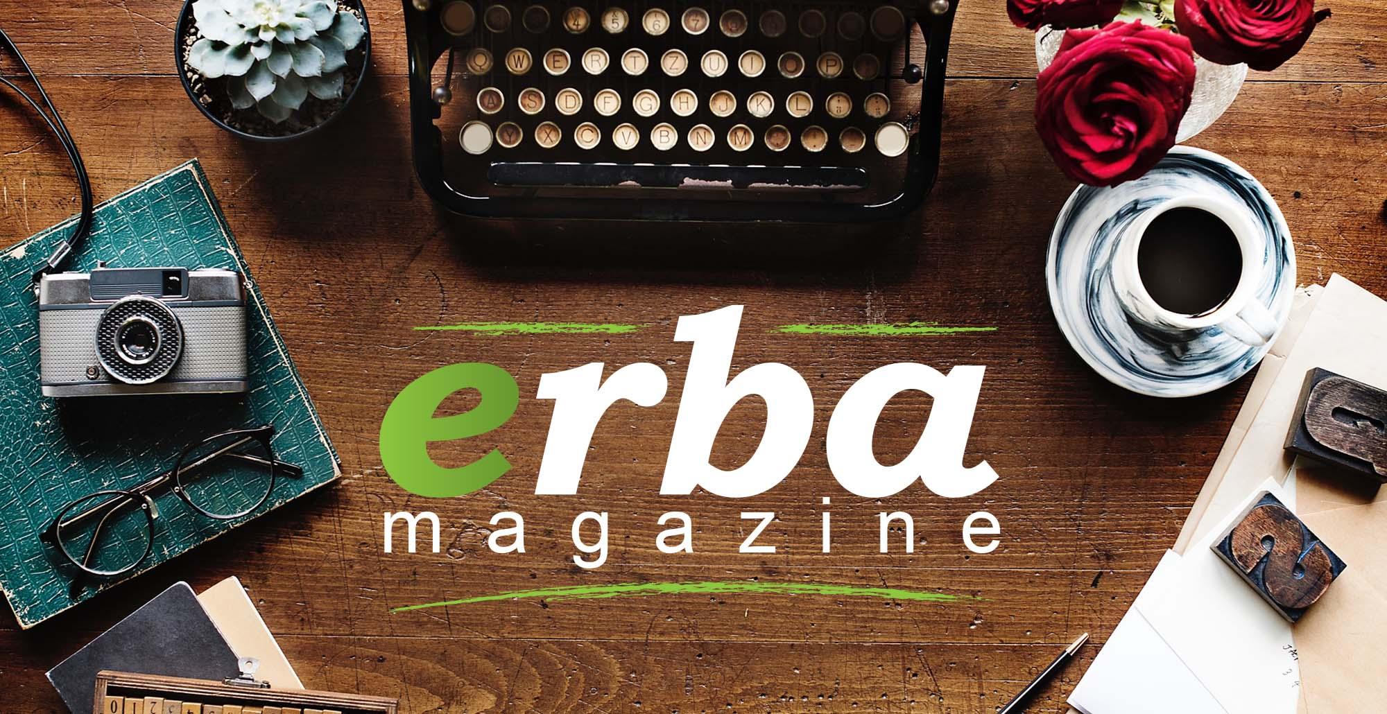 Foto scrivania con sopra taccuino, occhiali da vista, macchina da scrivere, fiori e caffè