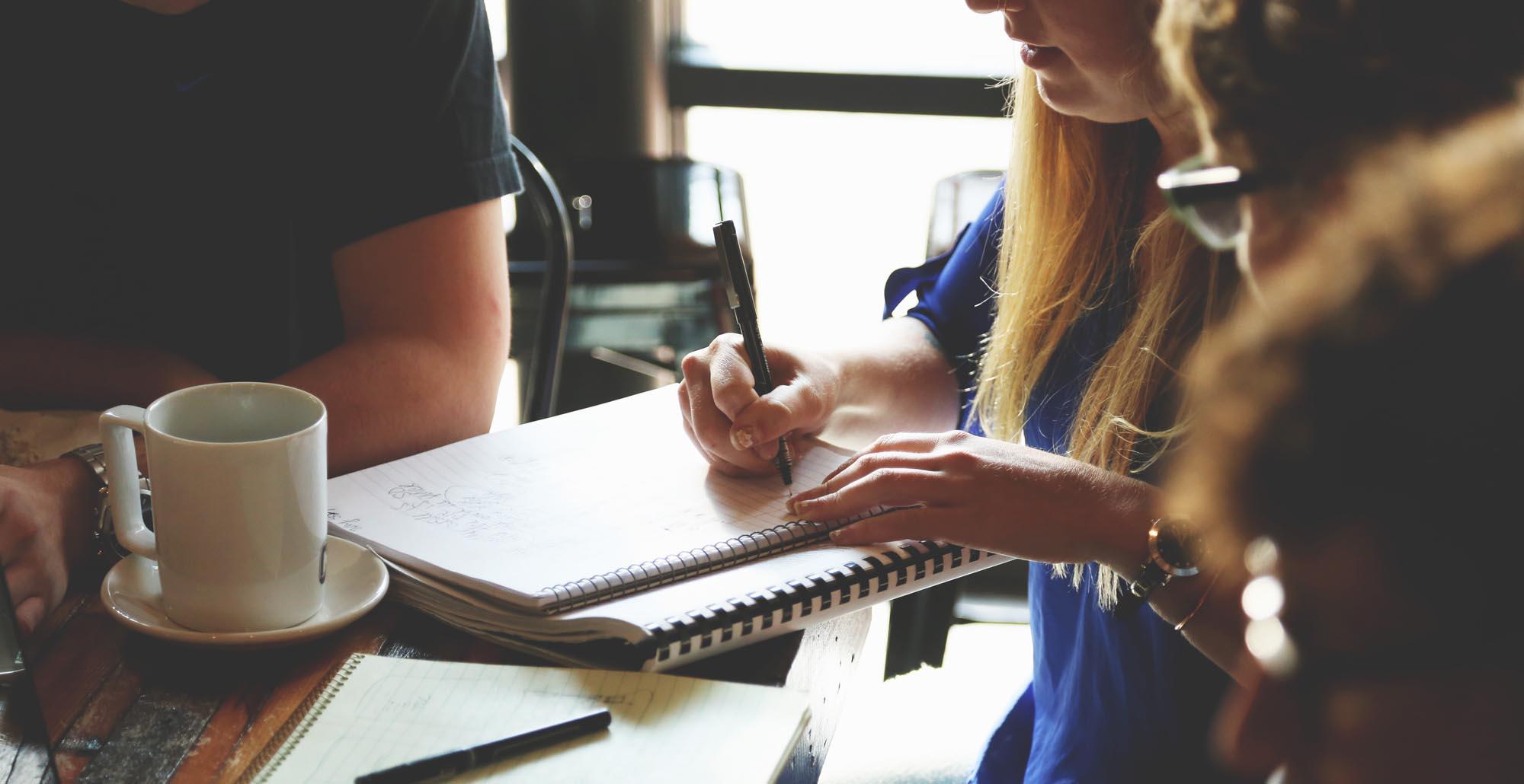 Foto di giovani che studiano insieme attorno ad un tavolo