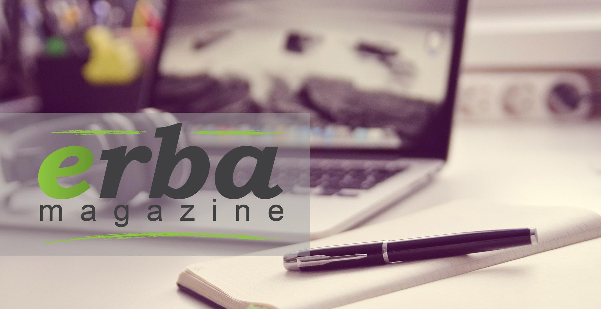 Foto bianco e nero di scrivania con pc, penna e taccuino con logo Erba Magazine