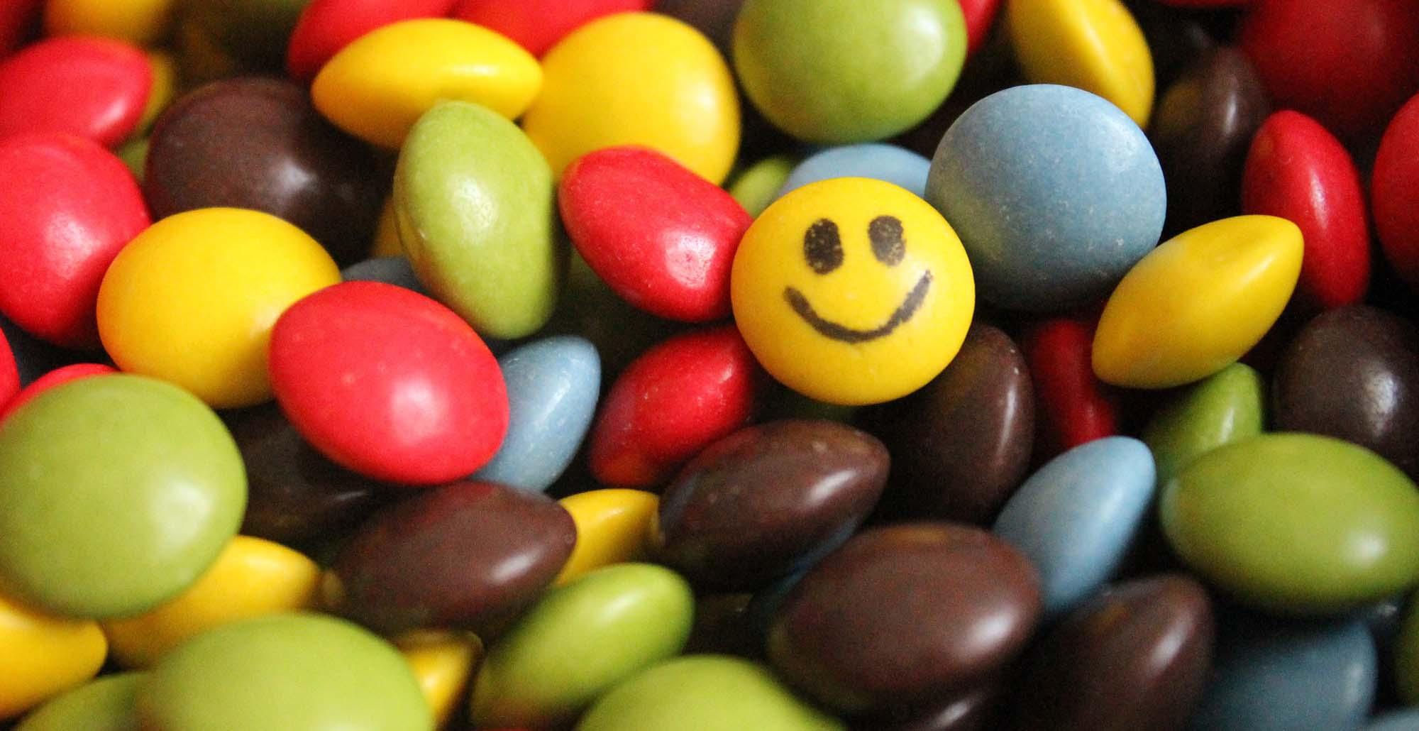 Foto con dettaglio di M&M's a colori con uno gialo su cui è disegnato uno smile