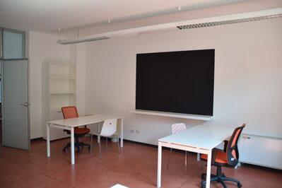 Foto interno spazio coworking piano terra con lavagna e postazioni lavoro