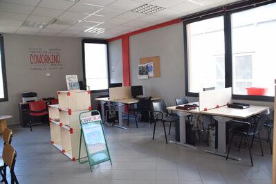 Foto interno spazio coworking con dettaglio di sticker murario con la scritta 'Coworking'
