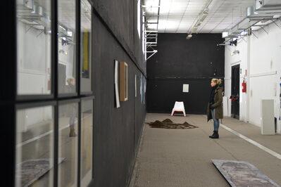 Foto interno corridoio espositivo durante una mostra con opere appese e un visitatore