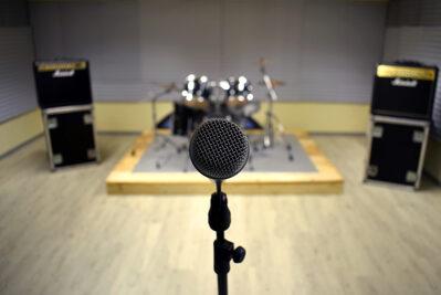 Foto dell'interno delle sale prova con in primo piano un microfono e sullo sfondo batteria e casse