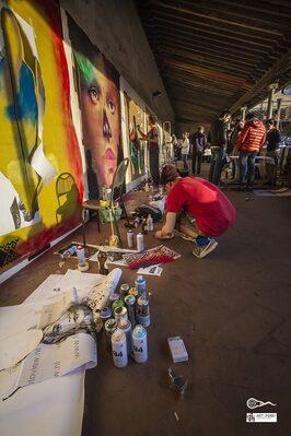 Writer in ginocchio che prova le bombolette dei colori e opere di diversi artisti lungo tutta la parete di fronte