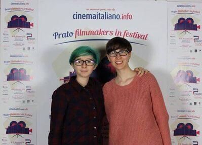 Foto delle ragazze che hanno realizzato il corto con sullo sfondo la grafica di Prato Filmmakers in Festival