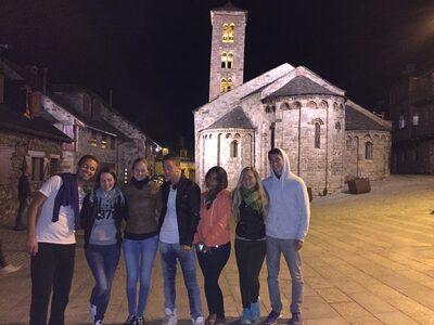 Foto notturna del volontario con altri sette ragazzi con sullo sfondo il paese e la chiesa illuminati