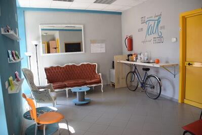 Foto interno saletta relax dello spazio coworking con divano e piccolo bar