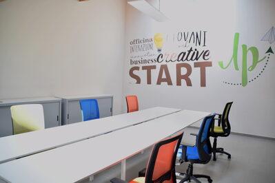 Foto interno spazio coworking con tavolo riunioni e sedie girevoli