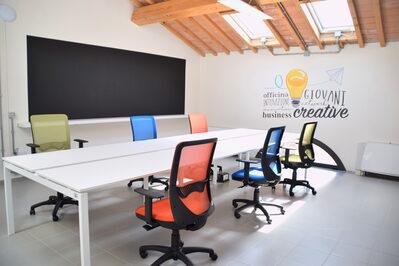 Foto interno spazio coworking con lavagna, tavolo riunioni e sedie girevoli